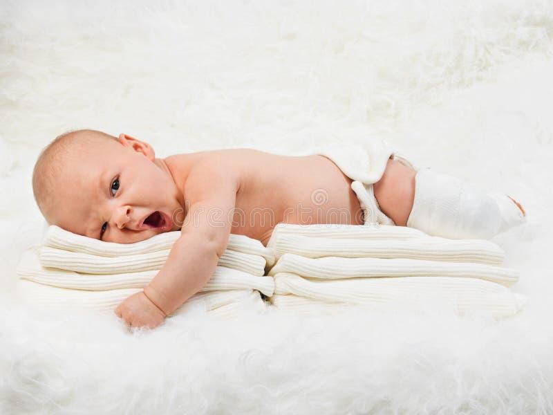 Νέος - γεννημένο αγοράκι που χασμουριέται στο κάλυμμα γουνών στοκ εικόνα