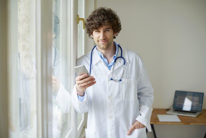 Νέος γιατρός με το κινητό τηλέφωνο στοκ εικόνες