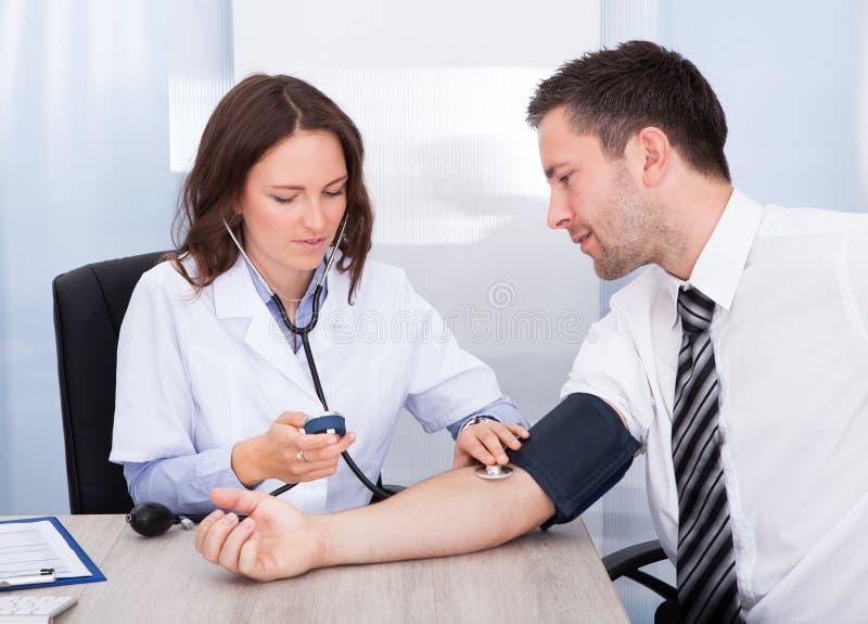 Νέος γιατρός που ελέγχει τη πίεση του αίματος στοκ εικόνα