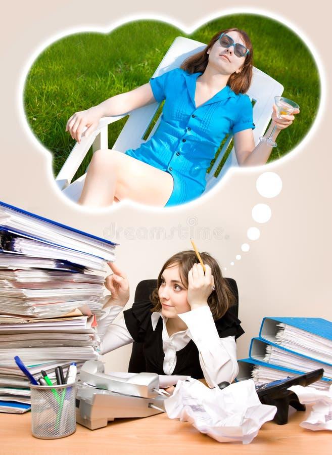Νέος γραμματέας με πολλούς φακέλλους που ονειρεύεται ένα καλοκαίρι στοκ εικόνες