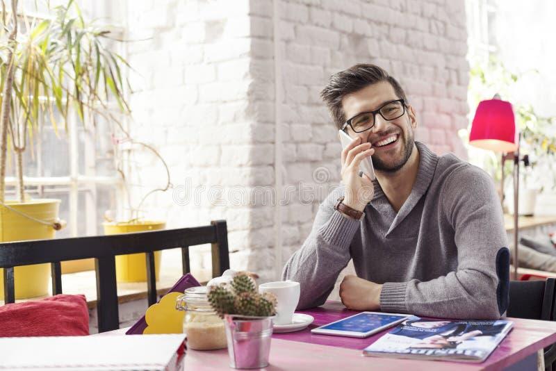 Νέος γραφικός σχεδιαστής με το τηλέφωνο στοκ εικόνες