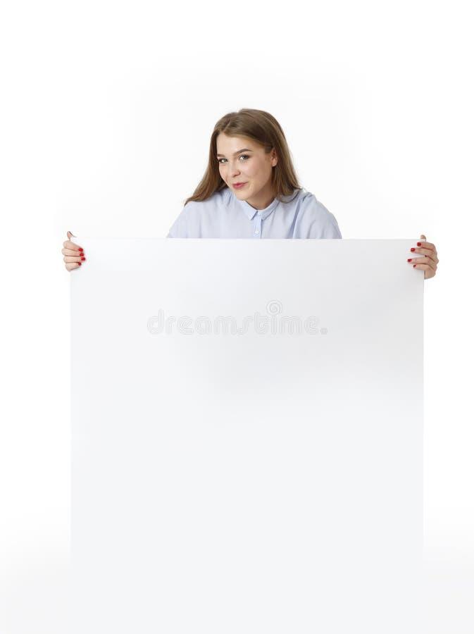 Νέος γυναικών πίνακας σημαδιών εκμετάλλευσης κενός λευκός στον περιστασιακό ιματισμό Απομονωμένο πορτρέτο στούντιο στοκ εικόνα με δικαίωμα ελεύθερης χρήσης