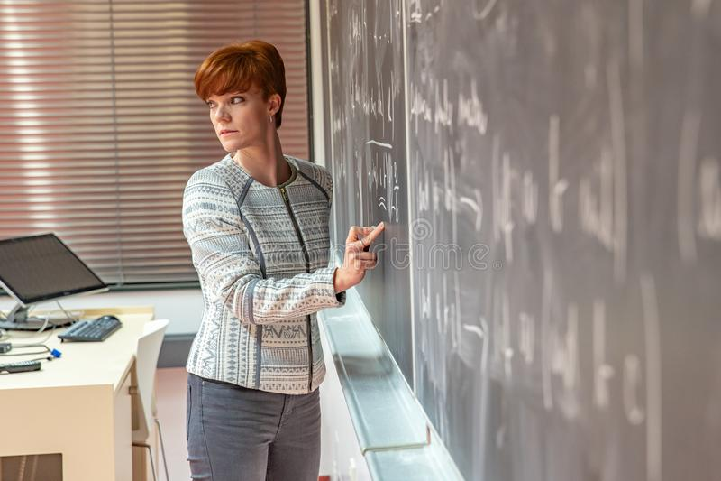 Νέος δάσκαλος γυναικών στο κολλέγιο Οδηγία σε μια πανεπιστημιακή τάξη Πίνακας που περιγράφεται από την κιμωλία Προβολή από στοκ εικόνες με δικαίωμα ελεύθερης χρήσης