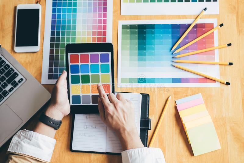 Νέος δημιουργικός γραφικός σχεδιαστής που χρησιμοποιεί την ταμπλέτα γραφικής παράστασης στο choosin στοκ εικόνα με δικαίωμα ελεύθερης χρήσης