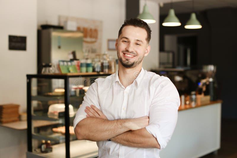 Νέος διοικητής που στέκεται με στον καφέ και που φορά το άσπρο πουκάμισο στοκ εικόνα με δικαίωμα ελεύθερης χρήσης