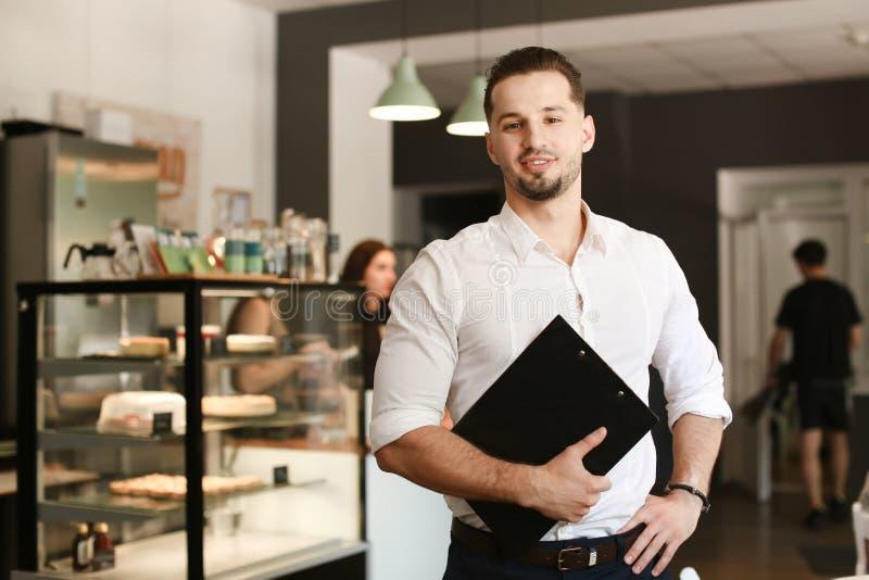 Νέος διοικητής που στέκεται με το μαύρο φάκελλο στον καφέ στοκ εικόνα με δικαίωμα ελεύθερης χρήσης
