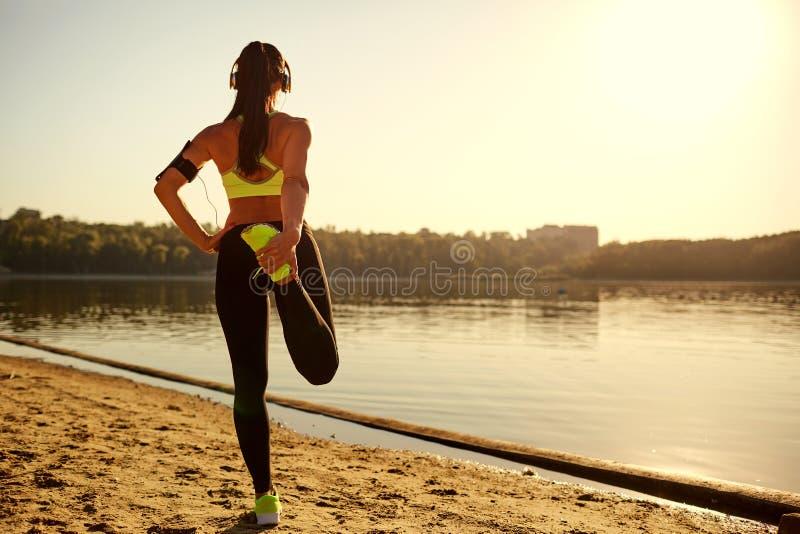 Νέος δρομέας γυναικών που κάνει την προθέρμανση που τεντώνει τα πόδια της σε ένα πάρκο στοκ φωτογραφία με δικαίωμα ελεύθερης χρήσης