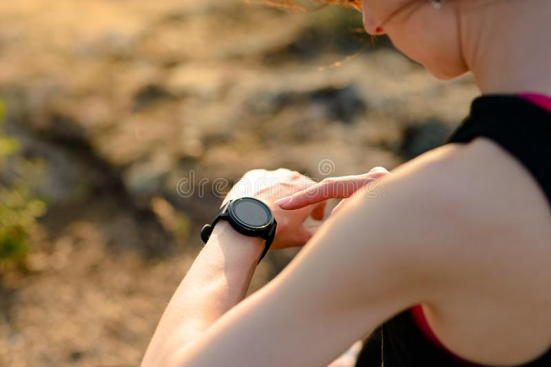 Νέος δρομέας γυναικών που χρησιμοποιεί Multisport Smartwatch στο ίχνος ηλιοβασιλέματος Κινηματογράφηση σε πρώτο πλάνο του χεριού  στοκ εικόνα με δικαίωμα ελεύθερης χρήσης