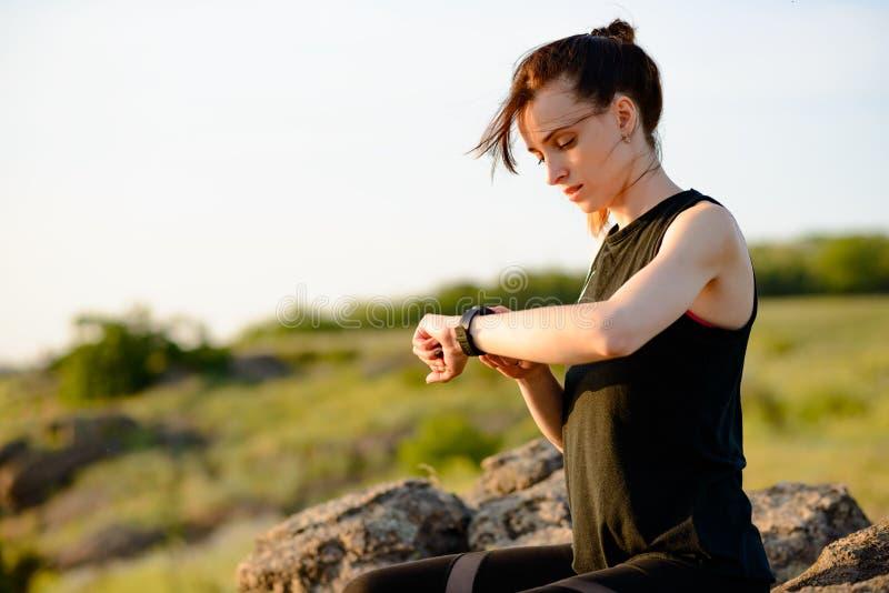 Νέος δρομέας γυναικών που χρησιμοποιεί Multisport Smartwatch στο ίχνος ηλιοβασιλέματος Κινηματογράφηση σε πρώτο πλάνο του χεριού  στοκ φωτογραφίες