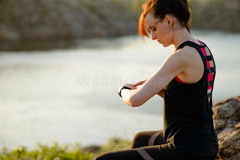 Νέος δρομέας γυναικών που χρησιμοποιεί Multisport Smartwatch στο ίχνος ηλιοβασιλέματος Κινηματογράφηση σε πρώτο πλάνο του χεριού  στοκ εικόνες