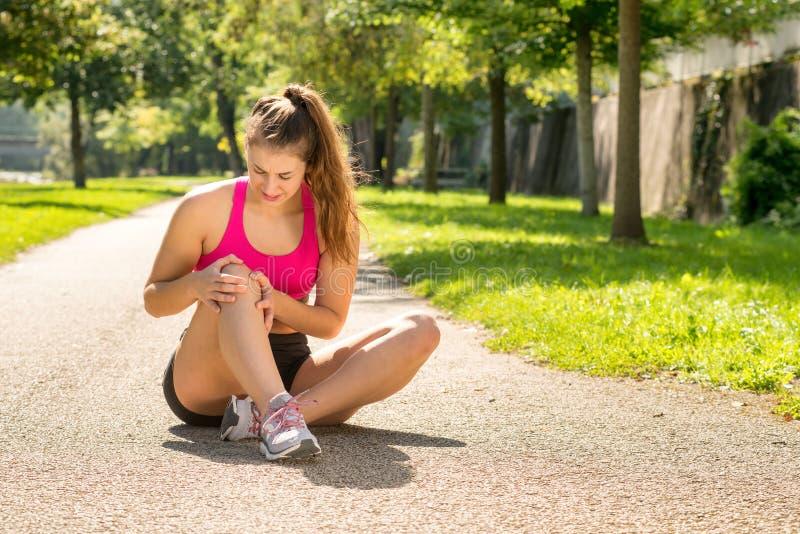 Νέος δρομέας γυναικών σχετικά με το γόνατο στον πόνο υπαίθρια στοκ φωτογραφίες με δικαίωμα ελεύθερης χρήσης