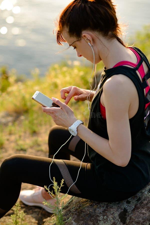 Νέος δρομέας γυναικών χρησιμοποιώντας Smartphone και ακούοντας τη μουσική στο ηλιοβασίλεμα στο ίχνος βουνών E στοκ εικόνα με δικαίωμα ελεύθερης χρήσης