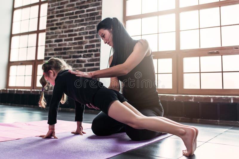Νέος εκπαιδευτής που βοηθά το μικρό κορίτσι που κάνει την άσκηση σανίδων στην αθλητική λέσχη στοκ φωτογραφία