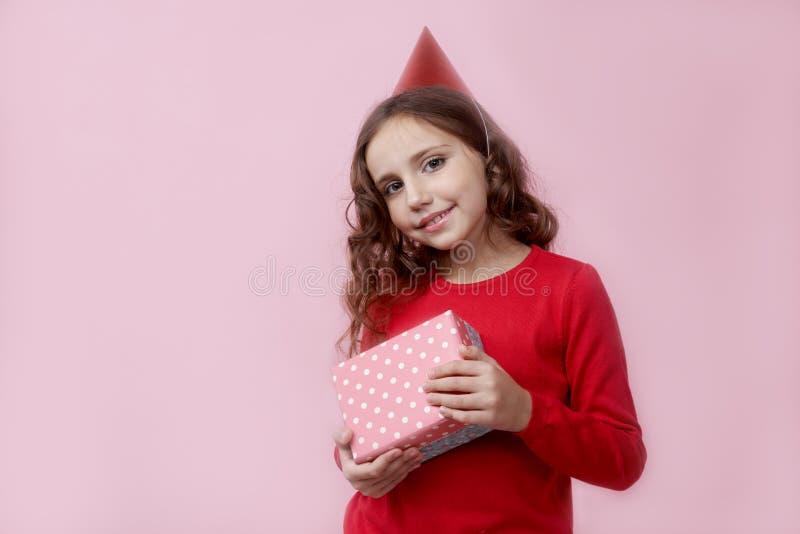 Νέος ελκυστικός έφηβος κοριτσιών με τη μακριά σγουρή τρίχα που χαμογελά ευρέως με τα δόντια που σταθερά ένα κιβώτιο δώρων στοκ φωτογραφία