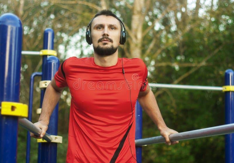 Νέος ελκυστικός αθλητής ατόμων που ασκεί την ώθηση επάνω στο εξωτερικό στοκ εικόνες