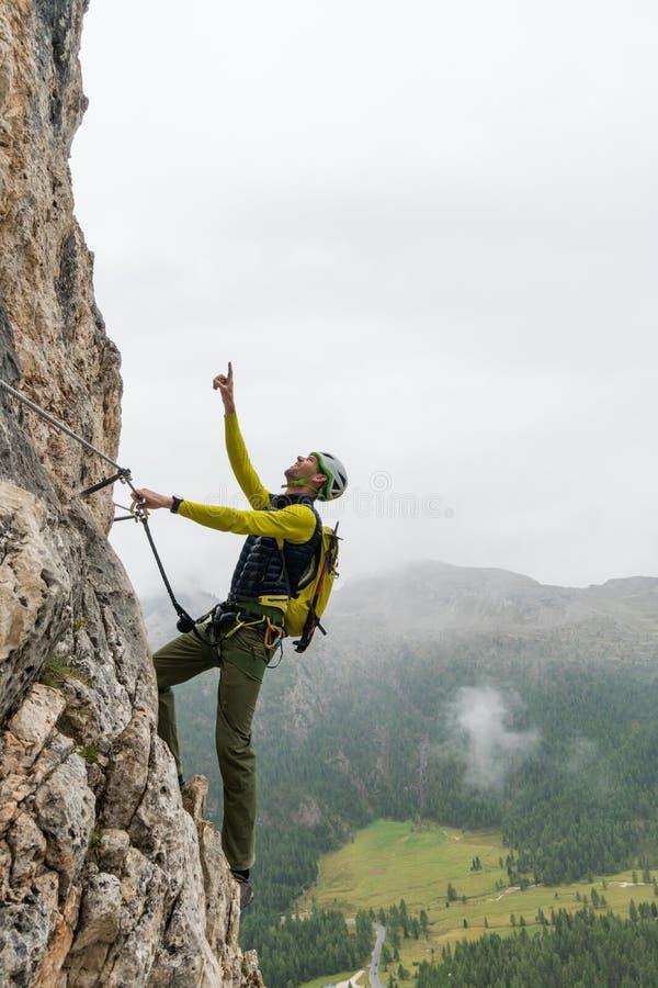 Νέος ελκυστικός αρσενικός ορειβάτης βουνών στους δολομίτες της Ιταλίας που δείχνει την κορυφή στοκ εικόνες με δικαίωμα ελεύθερης χρήσης