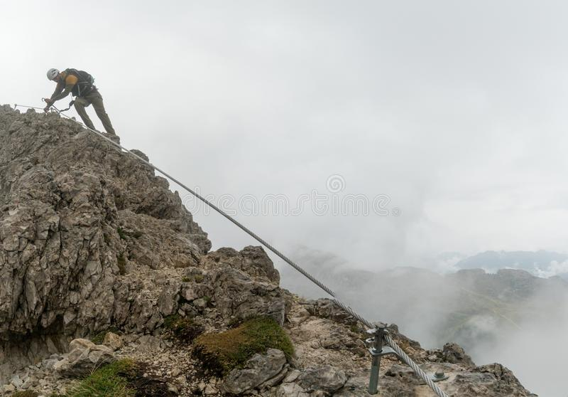 Νέος ελκυστικός αρσενικός ορειβάτης βουνών στους δολομίτες της Ιταλίας που δείχνει την κορυφή στοκ εικόνα με δικαίωμα ελεύθερης χρήσης