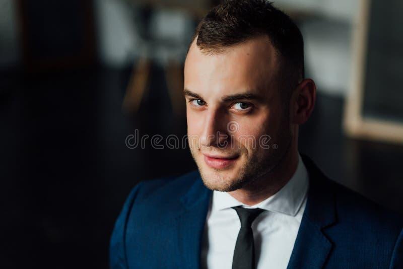 Νέος ελκυστικός και βέβαιος επιχειρηματίας στο μπλε κοστούμι και το μαύρο δεσμό στοκ εικόνα με δικαίωμα ελεύθερης χρήσης