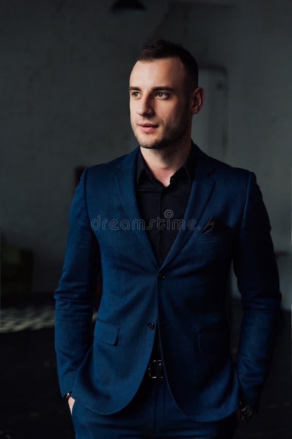 Νέος ελκυστικός και βέβαιος επιχειρηματίας στο μπλε κοστούμι και το μαύρο δεσμό στοκ φωτογραφία