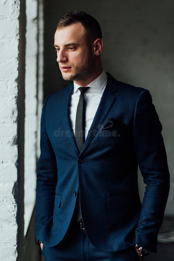 Νέος ελκυστικός και βέβαιος επιχειρηματίας στο μπλε κοστούμι και το μαύρο δεσμό στοκ εικόνα