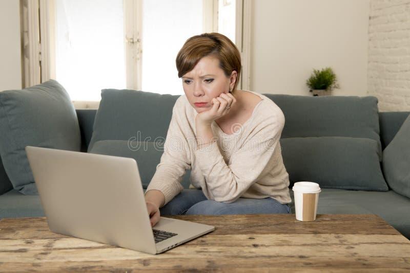 Νέος ελκυστικός και πολυάσχολος καναπές καναπέδων γυναικών στο σπίτι που κάνει κάποια εργασία φορητών προσωπικών υπολογιστών στην στοκ φωτογραφία
