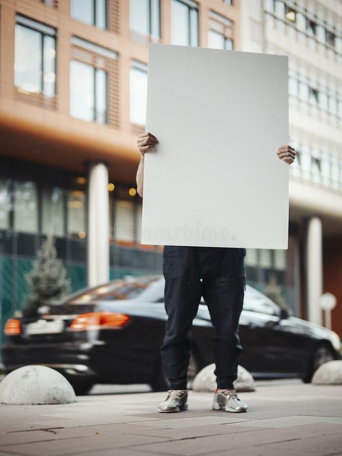 Νέος ελκυστικός κενός καμβάς εκμετάλλευσης ατόμων στην οδό δίπλα στο κόκκινο κτήριο στοκ εικόνα με δικαίωμα ελεύθερης χρήσης