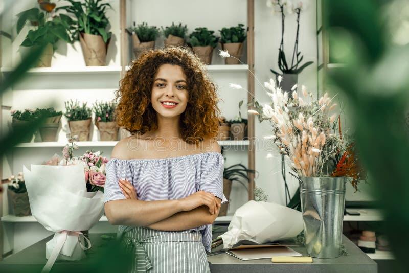 Νέος ελκυστικός σπουδαστής που απολαμβάνει τη μερικής απασχόλησης εργασία της στο μεγάλο floral κατάστημα στοκ φωτογραφία με δικαίωμα ελεύθερης χρήσης