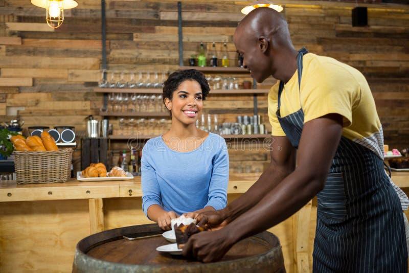 Νέος εξυπηρετώντας καφές barista στη γυναίκα στον πίνακα στοκ φωτογραφία