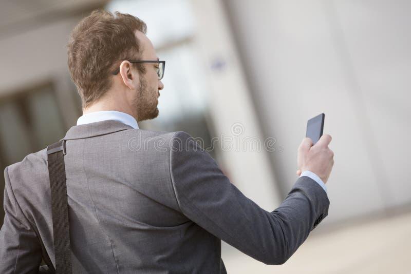 Νέος επαγγελματίας που χρησιμοποιεί το έξυπνο τηλέφωνο υπαίθρια στοκ φωτογραφία