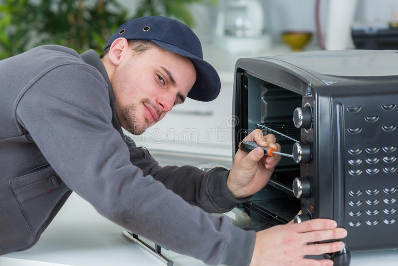 Νέος επισκευαστής που επισκευάζει το φούρνο με το κατσαβίδι στην κουζίνα πελατών στοκ εικόνες