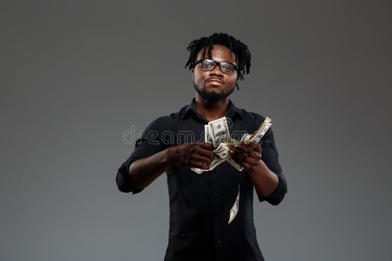 Νέος επιτυχής αφρικανικός επιχειρηματίας που ρίχνει τα χρήματα πέρα από το σκοτεινό υπόβαθρο στοκ εικόνες