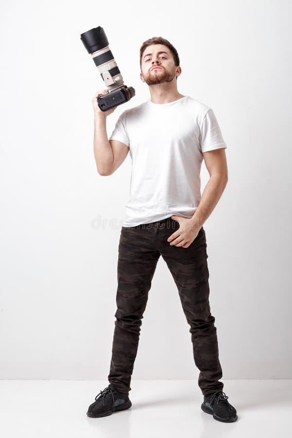 Νέος επιτυχής επαγγελματικός φωτογράφος στο digita χρήσης μπλουζών στοκ φωτογραφία με δικαίωμα ελεύθερης χρήσης