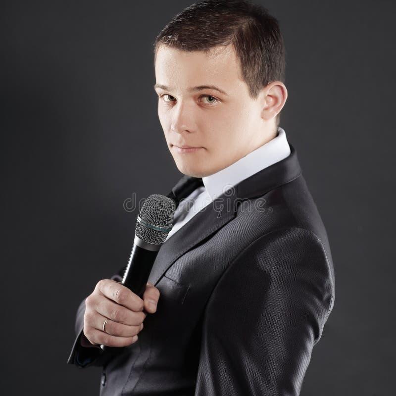 Νέος επιτυχής επιχειρηματίας με το μικρόφωνο απομονωμένος στο Μαύρο στοκ φωτογραφία