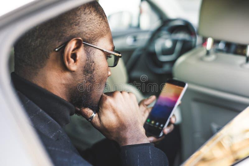 Νέος επιτυχής επιχειρηματίας που μιλά στην τηλεφωνική συνεδρίαση στο backseat ενός ακριβού αυτοκινήτου Διαπραγματεύσεις και επιχε στοκ εικόνες