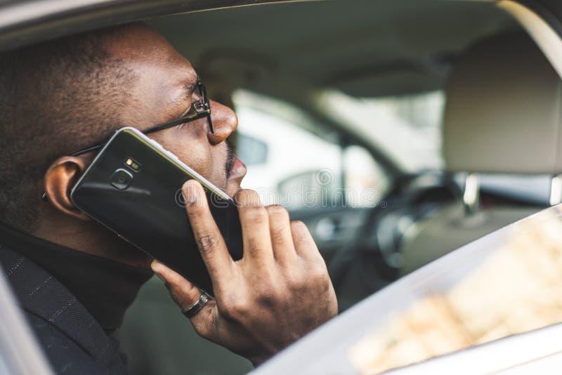 Νέος επιτυχής επιχειρηματίας που μιλά στην τηλεφωνική συνεδρίαση στο backseat ενός ακριβού αυτοκινήτου Διαπραγματεύσεις και επιχε στοκ φωτογραφία