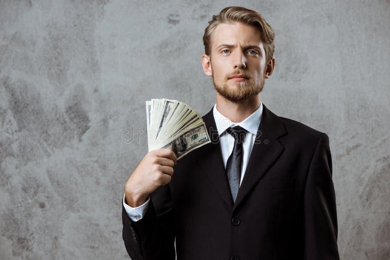 Νέος επιτυχής επιχειρηματίας στα χρήματα εκμετάλλευσης κοστουμιών πέρα από το γκρίζο υπόβαθρο στοκ φωτογραφία με δικαίωμα ελεύθερης χρήσης