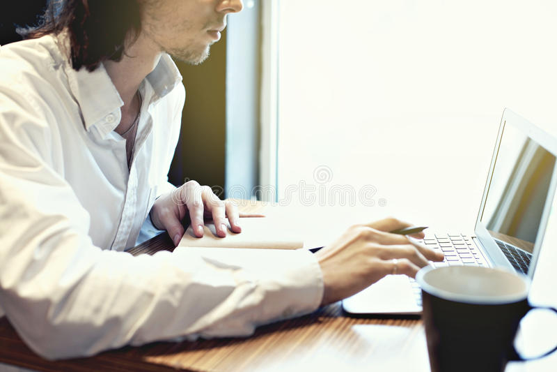 Νέος επιχειρηματίας ή σπουδαστής, μακρυμάλλες, γράψιμο εργασίας στο πληκτρολόγιο κοντά στο παράθυρο με το ανοικτό lap-top στοκ φωτογραφία