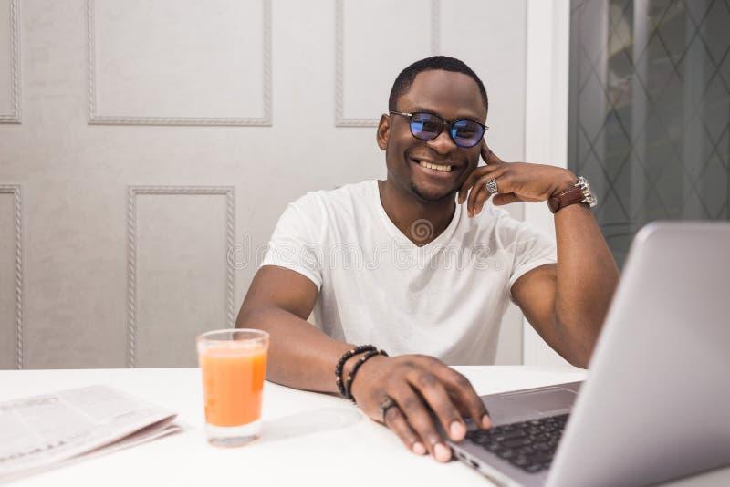 Νέος επιχειρηματίας αφροαμερικάνων που εργάζεται σε ένα lap-top στην κουζίνα σε ένα σύγχρονο εσωτερικό στοκ φωτογραφία με δικαίωμα ελεύθερης χρήσης