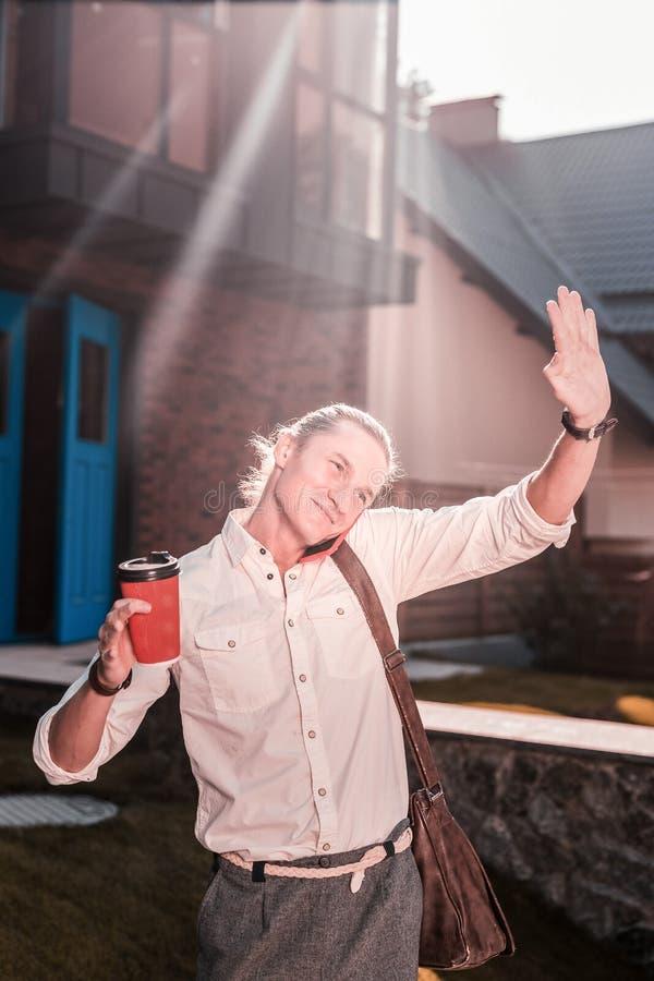 Νέος επιχειρηματίας με την καφετιά τσάντα δέρματος και γείτονας χαιρετισμού καφέ στοκ φωτογραφίες με δικαίωμα ελεύθερης χρήσης