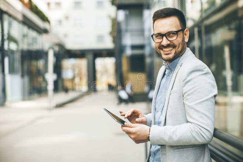 Νέος επιχειρηματίας με την ψηφιακή ταμπλέτα με το κτίριο γραφείων στοκ φωτογραφία με δικαίωμα ελεύθερης χρήσης