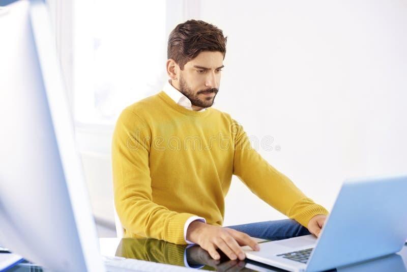 Νέος επιχειρηματίας με το σοβαρό πρόσωπο που λειτουργεί στο lap-top του στοκ φωτογραφία με δικαίωμα ελεύθερης χρήσης