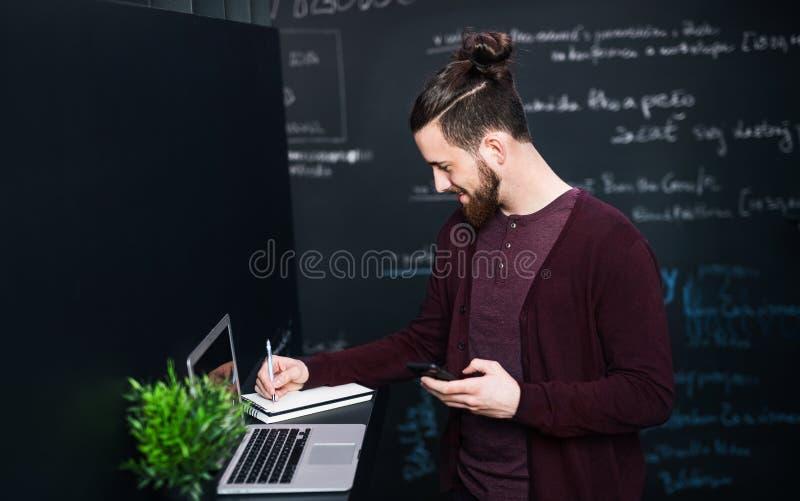 Νέος επιχειρηματίας με το lap-top στην αρχή, εργασία στοκ φωτογραφίες με δικαίωμα ελεύθερης χρήσης