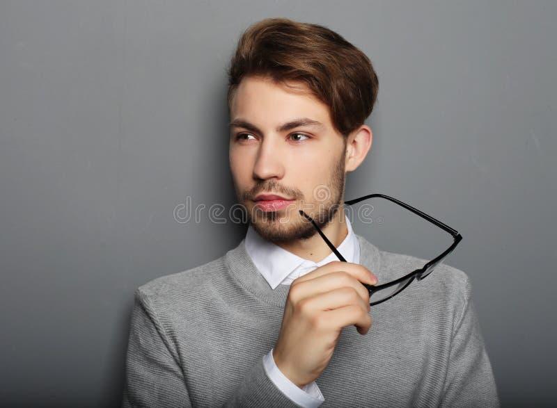 Νέος επιχειρηματίας με eyeglasses, που εξετάζουν τη κάμερα ενάντια στοκ φωτογραφία με δικαίωμα ελεύθερης χρήσης