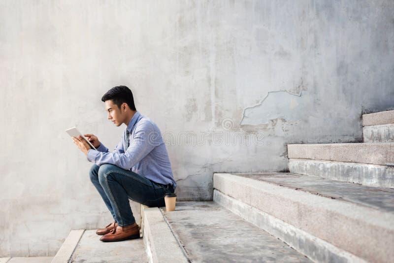 Νέος επιχειρηματίας που εγκαθιστά στο σκαλοπάτι εργαζόμενος στον ψηφιακό πίνακα στοκ εικόνα