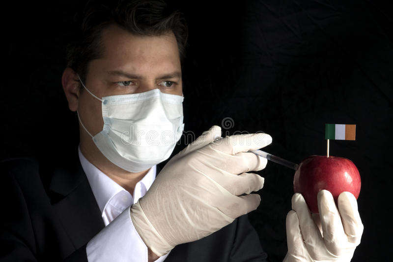 Νέος επιχειρηματίας που εγχέει τις χημικές ουσίες σε ένα μήλο με την ιρλανδική σημαία στοκ φωτογραφία με δικαίωμα ελεύθερης χρήσης