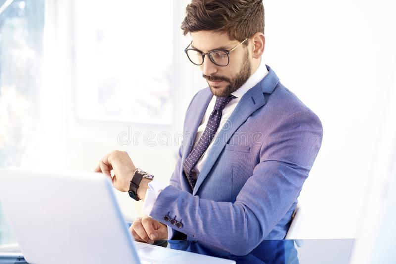Νέος επιχειρηματίας που ελέγχει το χρόνο στο wristwatch του στο γραφείο στοκ φωτογραφίες με δικαίωμα ελεύθερης χρήσης