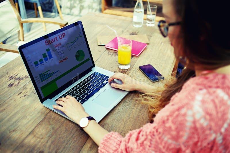 Νέος επιχειρηματίας που εργάζεται με τα στοιχεία στατιστικών και που αναλύει την απόδοση στο σημειωματάριό της στοκ φωτογραφίες