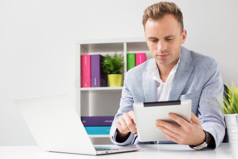 Νέος επιχειρηματίας που εργάζεται με τον υπολογιστή ταμπλετών στην αρχή στοκ εικόνες