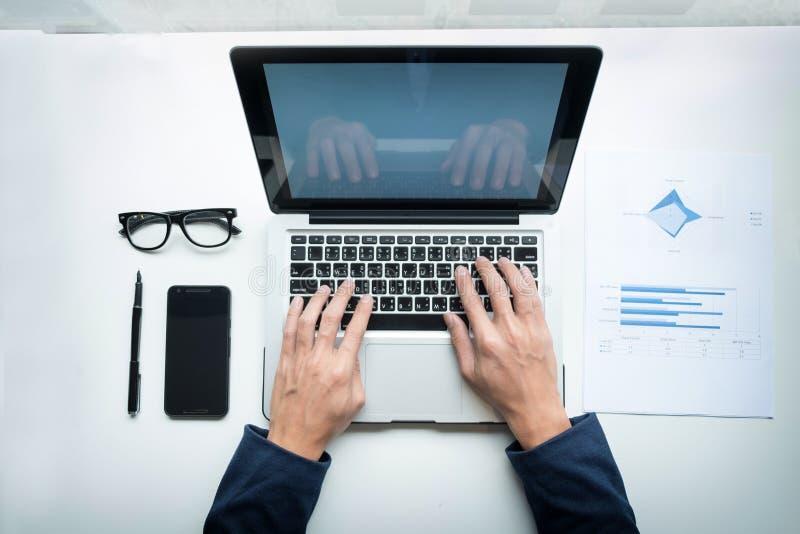 Νέος επιχειρηματίας που εργάζεται με το lap-top και το έξυπνος-τηλέφωνο στα des του στοκ φωτογραφίες με δικαίωμα ελεύθερης χρήσης