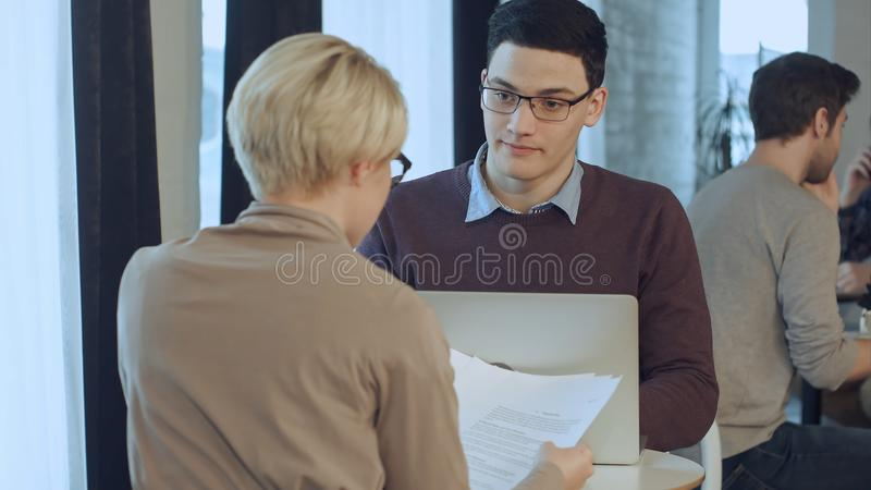 Νέος επιχειρηματίας που εργάζονται στο lap-top και επιχειρηματίας που εργάζεται με τα έγγραφα που κάθονται στο γραφείο απέναντι α στοκ εικόνες